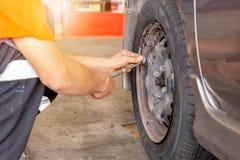 检查轮胎气压工作的汽车修理师在修理服务站 库存照片