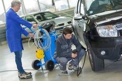 检查轮胎气压的学生和资深技工在汽车学校 库存照片