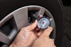 检查轮胎气压的技工使用测量仪 免版税库存照片