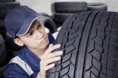 检查轮胎的年轻技工 图库摄影