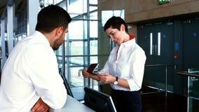 检查通勤者的护照母机场职员在报道登记柜台 股票录像