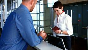 检查通勤者的护照母机场职员在报道登记柜台 股票视频