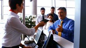检查通勤者的护照母机场职员在报道登记柜台 影视素材
