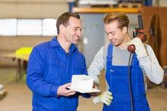 检查金属片断的两名钢建筑工人 免版税图库摄影