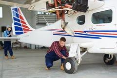 检查飞机的机械工在飞机棚 免版税库存照片