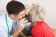 检查高级妇女的耳朵的英国医生 免版税库存照片