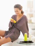 检查浴化妆用品的愉快的少妇在卫生间里 图库摄影