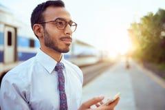 检查他在火车平台的确信的印地安商人巧妙的电话 免版税图库摄影