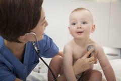 检查婴孩的心跳的微笑的医生与一个听诊器在医生办公室 免版税库存图片