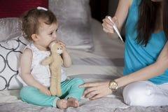 检查婴孩的温度 免版税库存照片