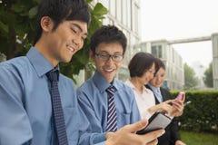检查他们手机和微笑的年轻商人 库存照片