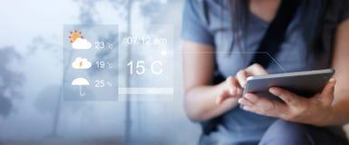 检查从片剂应用的天气预报的妇女 免版税库存照片