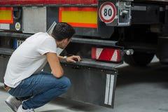 检查货物卡车的年轻技工 免版税库存照片