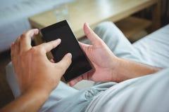 检查他的手机的人的中间部分 免版税库存照片