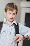 检查他的手表的男小学生在时间 免版税库存图片