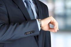 检查他的查出的时间手表白色的背景生意人 免版税库存照片