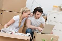 年轻检查他们的电子邮件的夫妇移动的房子 库存图片