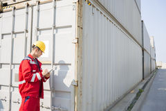 检查货箱的男性工作者,当写在剪贴板在运输的庭院时 库存照片