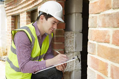 检查绝缘材料的建筑师在议院建筑时 免版税库存图片