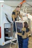 检查rv太阳能电池盘区的两名电子工作者 免版税库存照片