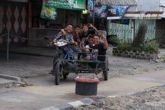 棉兰,北苏门答腊省,印度尼西亚- 2016年12月18日:摆在有推车的摩托车的五个孩子 免版税库存照片