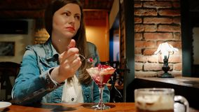 棉花夹克的俏丽的女孩吃点心用在咖啡馆的热巧克力 椅子内部最近的葡萄酒白色视窗 砖墙 股票录像