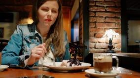 棉花夹克的俏丽的女孩吃点心用在咖啡馆的热巧克力 椅子内部最近的葡萄酒白色视窗 砖墙 股票视频