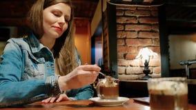 棉花夹克的俏丽的女孩用在咖啡馆的热巧克力 椅子内部最近的葡萄酒白色视窗 砖墙 影视素材