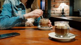 棉花夹克的俏丽的女孩用在咖啡馆的热巧克力 椅子内部最近的葡萄酒白色视窗 砖墙 股票录像