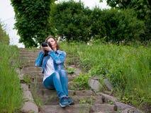 棉花夹克的美丽的女孩坐葡萄酒石头步和与一台专业照相机的采取照片在刮风的天气 库存照片