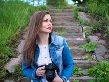 棉花夹克的美丽的女孩坐葡萄酒石头步和与一台专业照相机的采取照片在刮风的天气 免版税库存照片