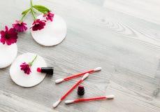 棉花盘,取消的构成海绵在花的背景 有棉花圆盘的秀丽女性手提取乳脂化妆水花 免版税库存图片