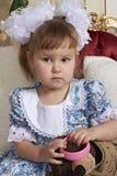 棉花礼服的女孩是拿着一个桃红色镯子和看观察者的一把白领和大白色弓 免版税库存照片