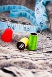 棉花针、卷轴和在牛仔布布料的一卷磁带 库存图片
