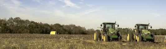 棉花领域全景与两台拖拉机的 免版税库存照片