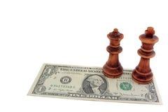 棋和美元:黑暗的国王和女王/王后一张美元票据的 免版税库存图片