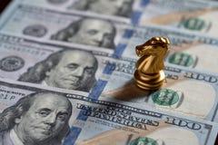 棋在美元钞票的骑士立场 商业投资和战略概念 免版税库存图片