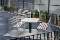 棋桌和空的长凳,在一个公园在威廉斯堡,布鲁克林,在一下雨天,纽约,美国 免版税库存照片