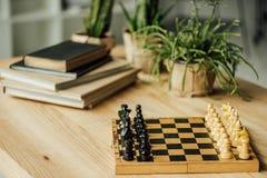 棋盘为在桌上的一场新的比赛设置了与书和盆的植物 库存图片