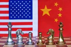 棋盘在美国和中国旗子背景,贸易战紧张情况概念的比赛片断 免版税库存图片