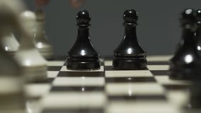 棋盘特写镜头有白色和黑棋子的 在一次紧张的比赛期间,对手采取典当 股票视频