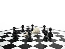 黑棋围拢的白色棋国王谎言在棋枰典当 免版税库存照片