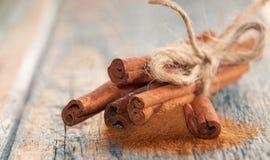 棍子和粉末芳香桂香在老木背景 免版税图库摄影