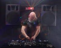 棍打有演奏在转盘的混合的音乐和跳舞在党从夜生活光的透镜火光的白色耳机的DJ 扩音器 图库摄影