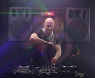 棍打有演奏音乐和跳舞在党从夜生活光的透镜火光的白色耳机的DJ 扩音器和激光支持 库存图片