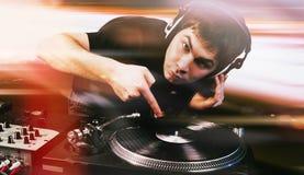 棍打演奏在乙烯基转盘的DJ混合的音乐 库存照片