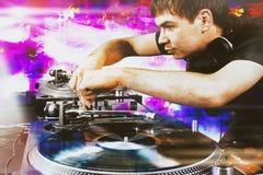 棍打演奏在乙烯基转盘的DJ混合的音乐 图库摄影