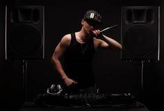 棍打演奏音乐和speking在党的DJ 在背景的大报告人 免版税库存照片