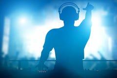棍打,迪斯科人的DJ使用的和混合的音乐 夜生活 免版税库存照片