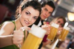 棒啤酒饮用的朋友 免版税库存照片